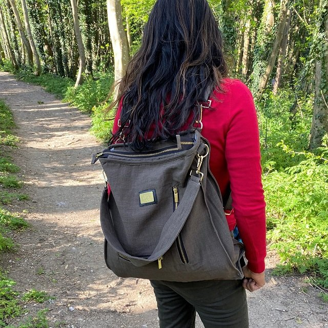 woman in red top with a canvas backpack style bag