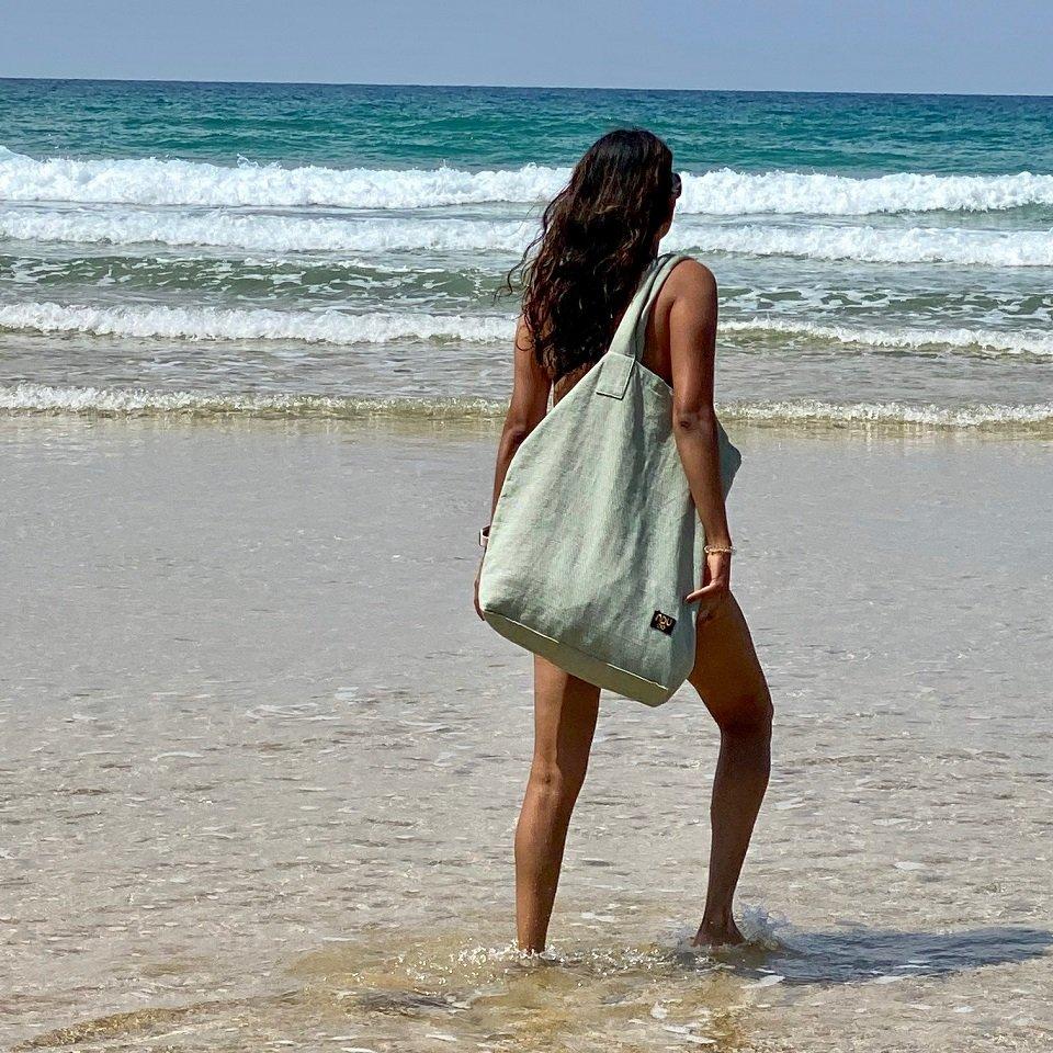 cotton canvas beach bag over a shoulder on a sandy uk beach
