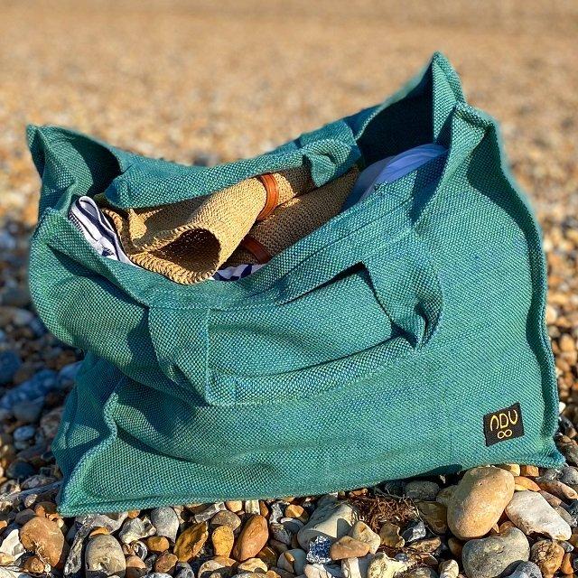 green reusable canvas beach bag on stone beach