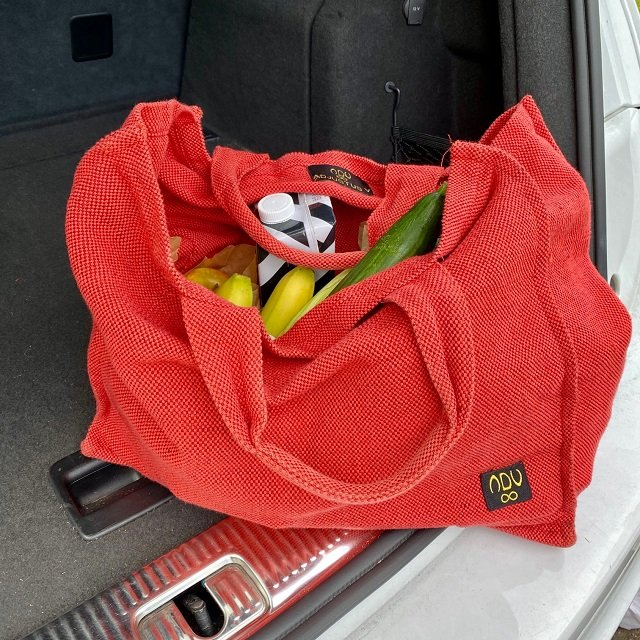 red reusable shopper bag filled up with grocery